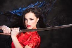 Woman in kimono with katana sword. Pretty kimono woman in action with katana/sword Royalty Free Stock Photography