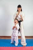 Woman in kimono posing with the child. Fighting position, active lifestyle, practicing fighting techniques Royalty Free Stock Photo