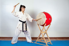 Woman in a kimono pounding the drum. Fighting position, active lifestyle, practicing fighting techniques Royalty Free Stock Images