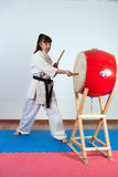 Woman in a kimono pounding the drum. Fighting position, active lifestyle, practicing fighting techniques Stock Photography