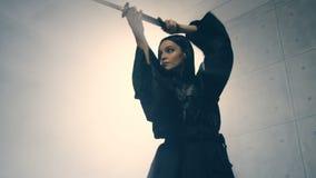 Woman in kimono practicing martial arts with katana
