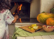 Cooking in the oven. Harvest. Vegetables and fruits are baked in the oven. Woman kindles a fire in the oven. Next to the table are pumpkins and apples. Vintage stock image