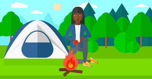 Woman kindling fire. An african-american woman kindling a fire on the background of camping site with tent vector flat design illustration. Horizontal layout Stock Images