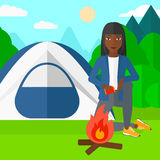 Woman kindling fire. An african-american woman kindling a fire on the background of camping site with tent vector flat design illustration. Square layout Royalty Free Stock Images