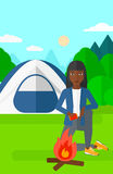 Woman kindling fire. An african-american woman kindling a fire on the background of camping site with tent vector flat design illustration. Vertical layout Royalty Free Stock Photos
