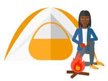 Woman kindling fire. An african-american woman kindling a fire in camp vector flat design illustration isolated on white background Stock Image