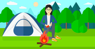 Woman kindling fire. An asian woman kindling a fire on the background of camping site with tent vector flat design illustration. Horizontal layout Royalty Free Stock Photo