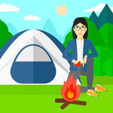 Woman kindling fire. An asian woman kindling a fire on the background of camping site with tent vector flat design illustration. Square layout Stock Photo