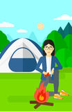 Woman kindling fire. An asian woman kindling a fire on the background of camping site with tent vector flat design illustration. Vertical layout Stock Photography