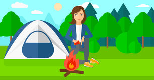 Woman kindling fire. A woman kindling a fire on the background of camping site with tent vector flat design illustration. Horizontal layout Stock Image