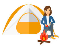 Woman kindling fire. A woman kindling a fire in camp vector flat design illustration isolated on white background Stock Photo