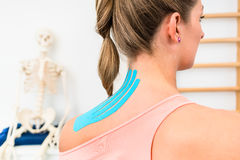 Woman with Kinesio tape on shoulder in physiotherapy. Woman from behind with Kinesio tape on shoulder in physiotherapy Royalty Free Stock Images