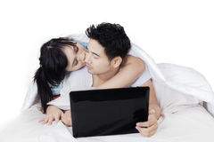 Woman kiss her husband with laptop on bed Stock Photos