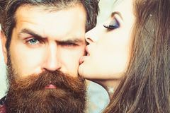 Woman kiss hipster with long beard, love. Sensual woman with makeup skin and bearded man. Couple in love and family. Woman kiss hipster with long beard, love stock image
