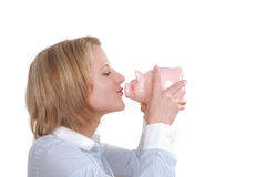 Woman kiss a piggy bank. Young woman kissing a big piggy bank on white background Royalty Free Stock Photos