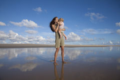 Woman kisses baby at reflect beach Royalty Free Stock Photos