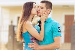 Woman kisses boyfriend on street Royalty Free Stock Image