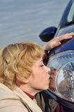 Woman kisses a car, Car Series. Blonde around headlight, blue and yellow colors skyline Stock Images