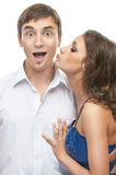 Woman kisses cheek surprised man Royalty Free Stock Photography