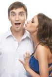 Woman kisses cheek surprised man Royalty Free Stock Photography