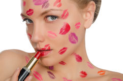 Woman with kisses on face holding lipstick Stock Photo