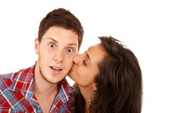 Woman kisses her boyfriend on the cheek Stock Photography