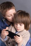 Woman kisses her little 4 year old son while he plays on her smartphone. Woman kisses her little 4 year old son dressed in a knitted cardigan, while he plays on stock image