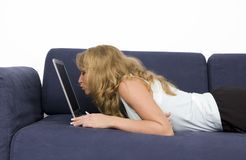 A woman kisses laptop. A woman on the sofa kisses laptop Royalty Free Stock Images