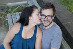 Woman kisses man on cheek Stock Images
