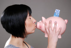 Woman kisses piggybank Royalty Free Stock Images