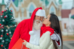 Woman kisses to Santa Clauss Stock Images