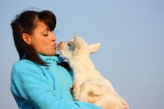 Woman kissing a baby goat Royalty Free Stock Photo