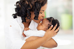 Woman kissing baby Royalty Free Stock Photography