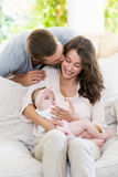 Woman kissing baby while man kissing her from behind Royalty Free Stock Photos