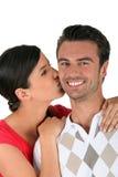 Woman kissing boyfriend Stock Photography