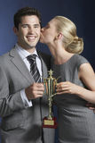 Woman Kissing Businessman As They Hold Trophy Royalty Free Stock Photos