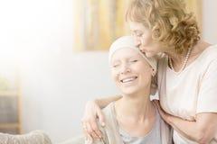 Woman kissing cancer survivor`s temple Stock Images