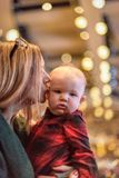 Woman kissing child in church on Christmas Eve. Woman holding and kissing baby on cheek indoors at Christmas Eve church service stock photo
