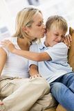 Woman kissing disgusted young boy in living room. On a sofa Royalty Free Stock Image