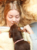 Woman kissing dog waking up in bed after sleeping. Royalty Free Stock Photography