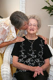 Woman Kissing Elderly Mother. A woman kisses her elderly mother in a portrait Stock Photography