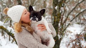 Woman kissing a french bulldog in the snow. With a forest behind stock image