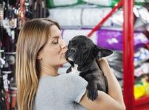 Woman Kissing French Bulldog At Store. Loving mid adult woman kissing French Bulldog at pet store Royalty Free Stock Image