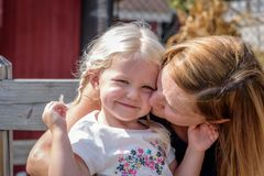 Woman kissing girl on the cheek royalty free stock photos