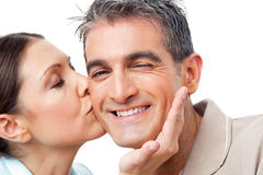 Woman kissing happy man on cheek. Elderly women in love kissing happy men on cheek Stock Image