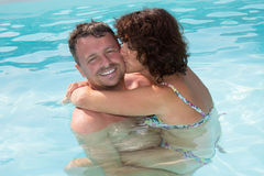 Woman kissing happy woman at pool in holiday Royalty Free Stock Images