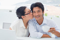 Woman kissing her boyfriend on the cheek having coffee Royalty Free Stock Image