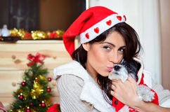 Woman kissing  her dog  dressed with red christmas hats Royalty Free Stock Image