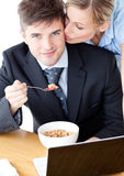 Woman kissing her eating businessman boyfriend Stock Images
