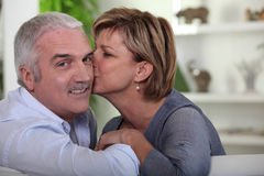 Woman kissing her husband. On the cheek Stock Image